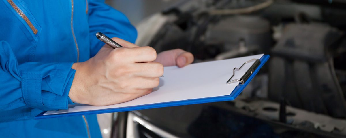 Young mechanic engineer taking a note on clipboard for examining a vehicle..