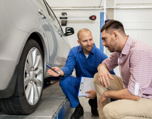 auto service, repair, maintenance and people concept - mechanic with clipboard showing tire to man or owner at car shop