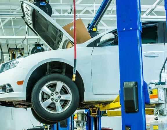 Broken Car in the Auto Service on Heavy Duty Car Lift.