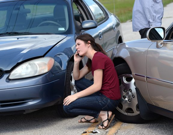Young woman making phone call after accident