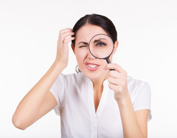 Beautiful funny girl searching with magnifier. White background.