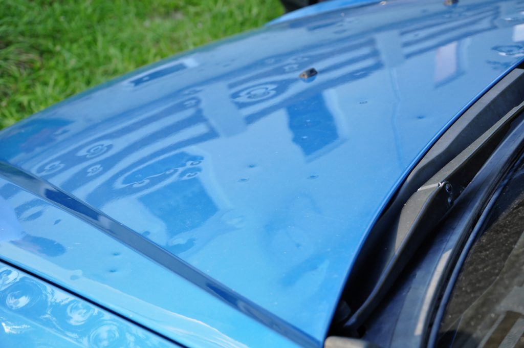 hail damage on the hood of a blue car